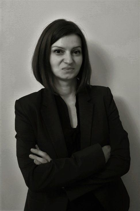 Kobieta z założonymi rękami, stojąca na tle ściany.