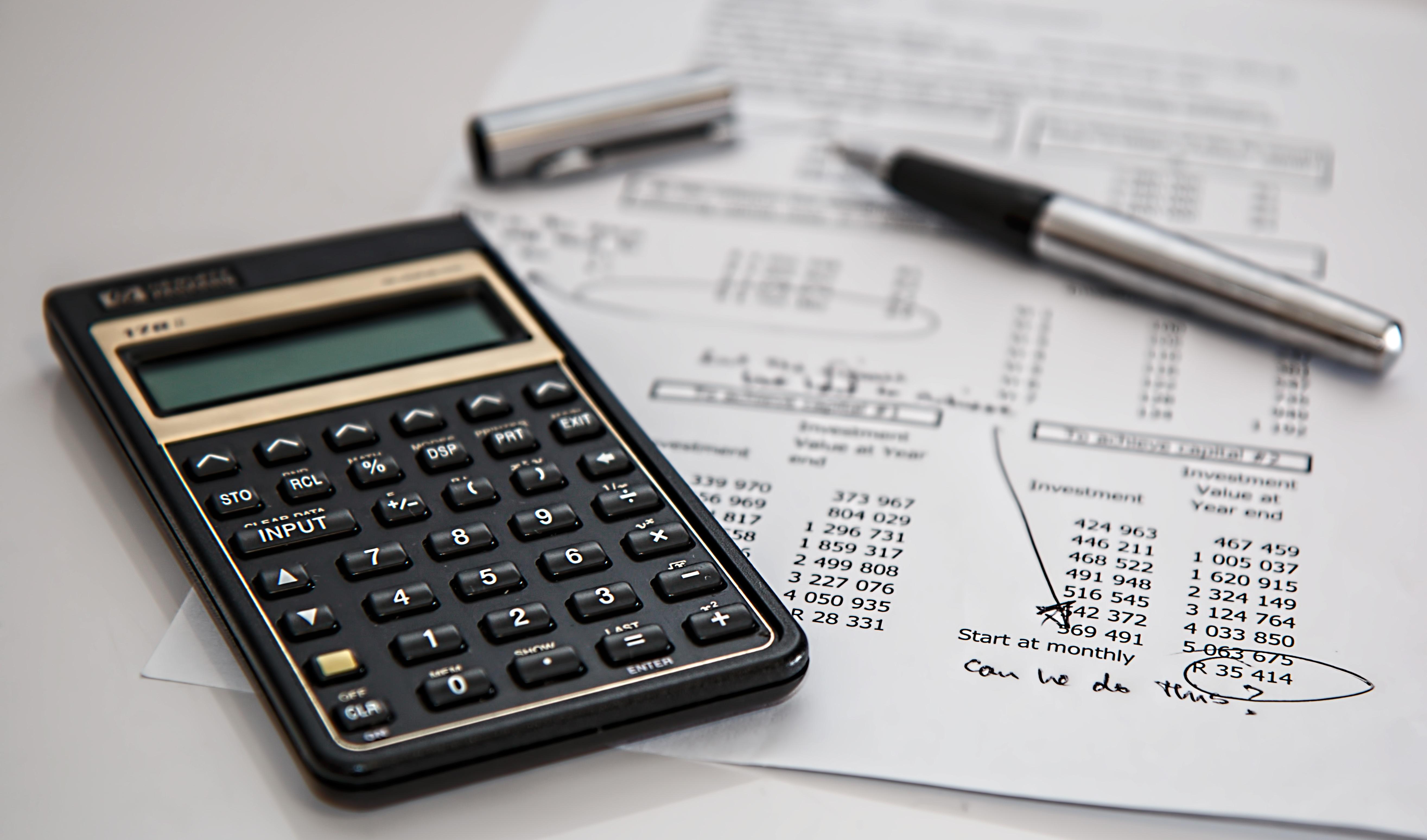 kalkulator ułożony na kartce papieru zawierającej obliczenia