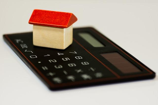 zabawkowy domek, ułożony na kalkutorze, ilutstruje artykuł dot. kredyt hipoteczny po rozwodzie